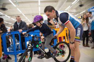 Thomas Copponi aidant un petit garcon à rester en équilibre sur son vélo