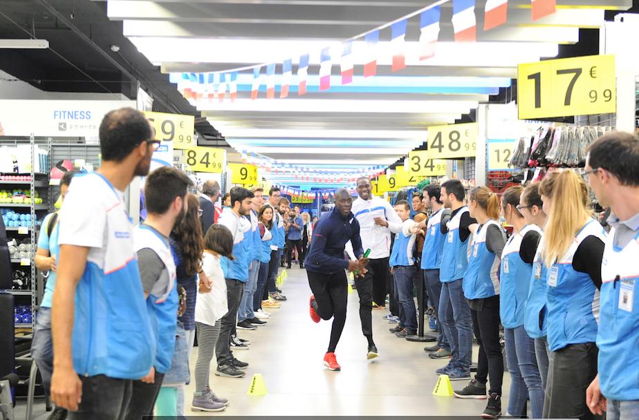 Les deux champions d'europe font un relais dans l'allée centrale du magasin